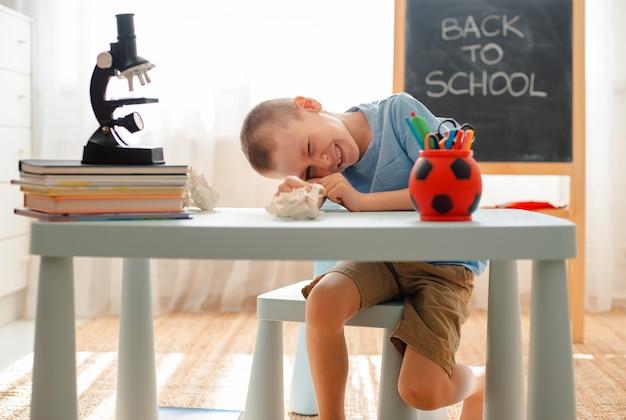 El estudiante se sienta a la mesa y participa en material educativo.