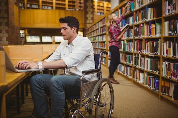 Estudiante en silla de ruedas escribiendo en su computadora portátil mientras que una mujer busca libros en la biblioteca