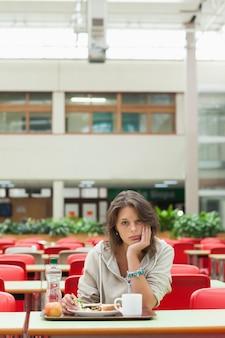 Estudiante sombrío en la cafetería con bandeja de comida