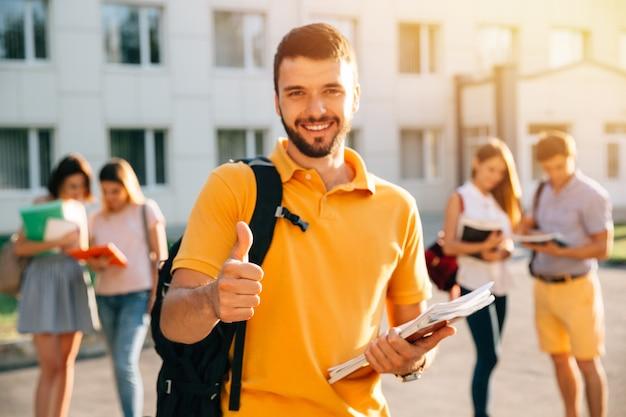 Estudiante sonriente atractivo joven que muestra el pulgar para arriba al aire libre en campus en la universidad.