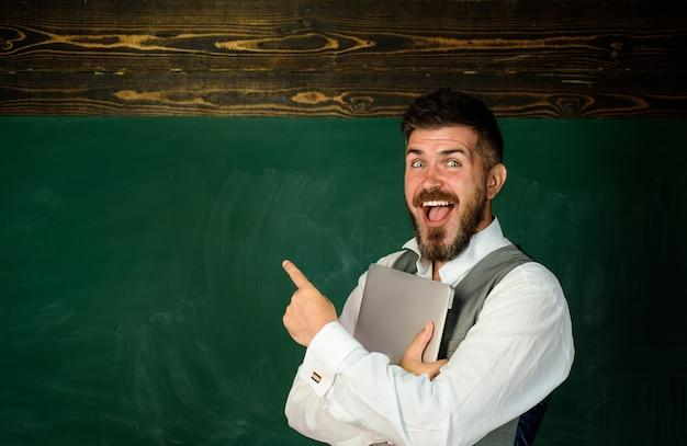 Estudiante sonriente en el aula estudiante masculino en el aula con la enseñanza de la escuela de educación portátil a la gente