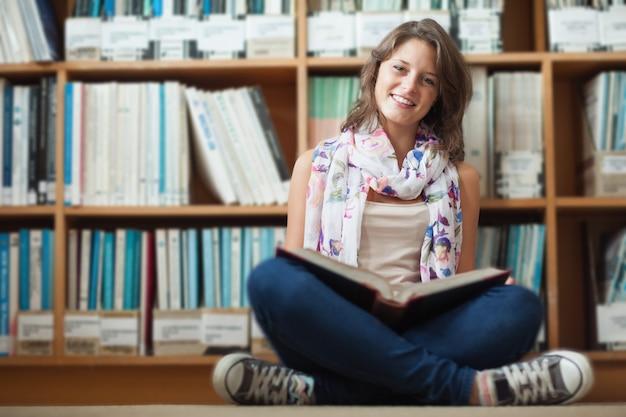 Estudiante sonriente contra la estantería leyendo un libro en el piso de la biblioteca