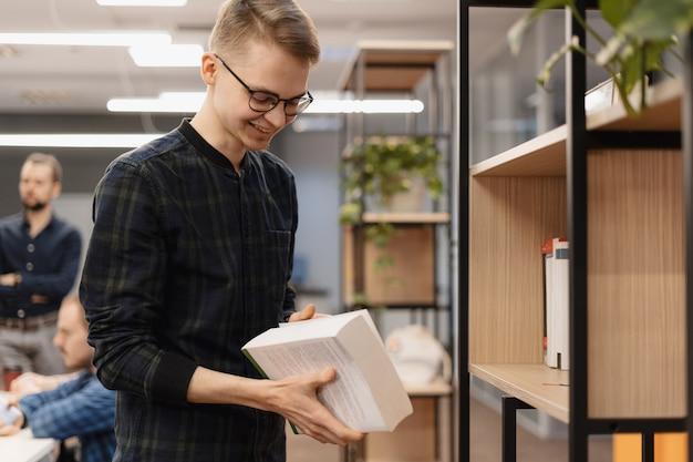 Un estudiante sonriente con un libro en sus manos.