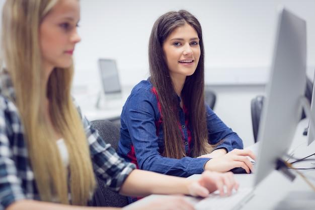 Estudiante sonriente que trabaja en la computadora en la universidad