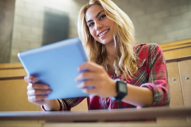 Estudiante sonriente que usa la tableta en sala de conferencias