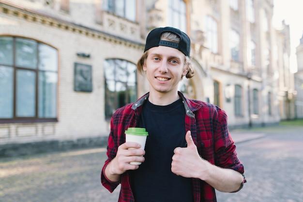 Estudiante sonriente sostiene café y muestra su dedo frente a la universidad.