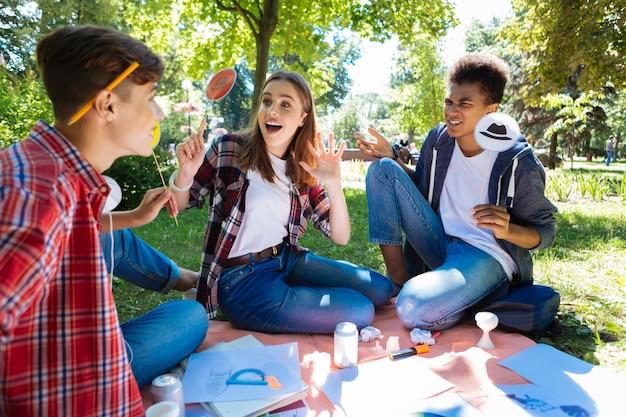 Estudiante sorprendido. estudiante de cabello oscuro con camisa blanca que se siente muy sorprendido mientras intercambia ideas con amigos