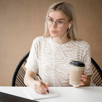Estudiante sosteniendo café y tomando notas