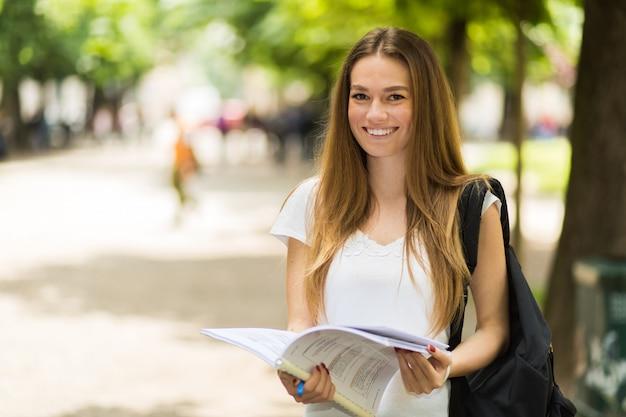 Estudiante sosteniendo un libro al aire libre en el parque y sonriendo
