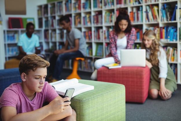 Estudiante mediante teléfono móvil en la biblioteca