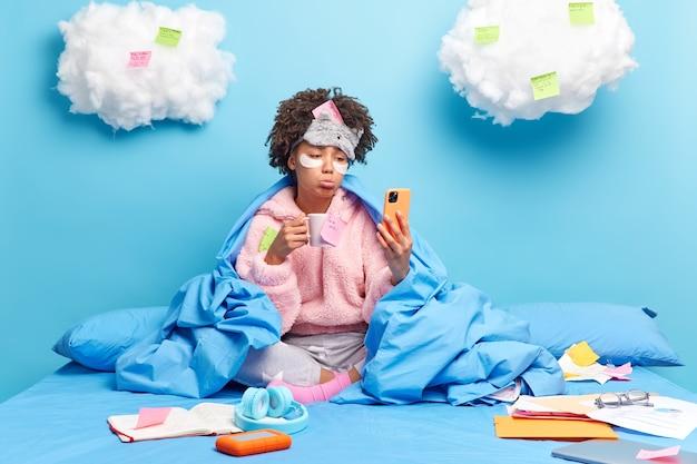 El estudiante tiene una lección en línea a través de un teléfono inteligente estudios desde su casa durante la cuarentena tiene una expresión triste al descubrir los resultados del examen bebe café