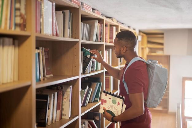 Estudiante de tiro medio buscando libros