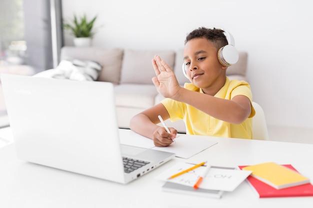 Estudiante de tiro medio saludando a laptop
