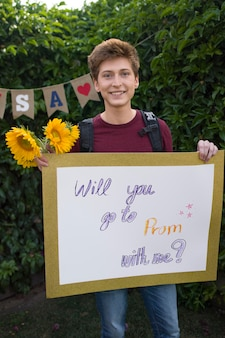Estudiante de tiro medio sosteniendo pancarta