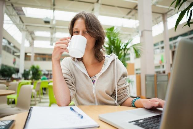 Estudiante tomando café mientras usa la computadora portátil en la mesa de la cafetería