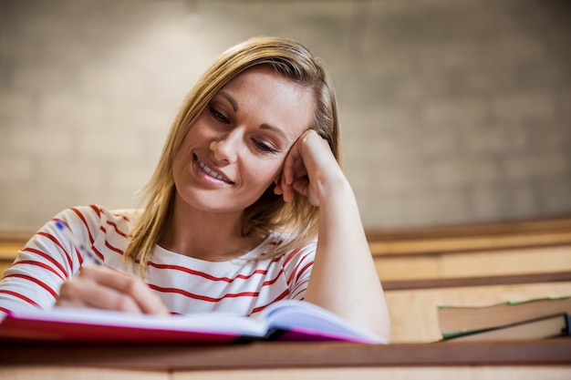 Estudiante tomando notas en una clase en la universidad