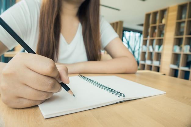 Estudiante tomando notas de un libro en la biblioteca. mujer asiática joven que se sienta en la mesa que hace asignaciones en biblioteca de la universidad. vintage efecto estilo imágenes.