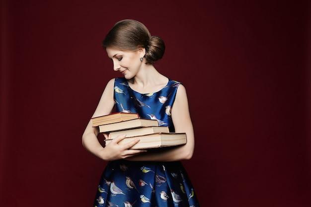 Estudiante trabajadora en vestido azul manteniendo libros en las manos y mirando a la cámara hermosa ...