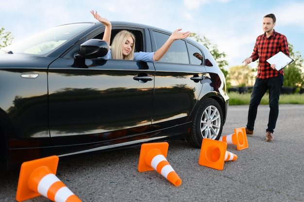 Estudiante triste en coche e instructor, todos los conos de tráfico están caídos, lección en la escuela de conducción.