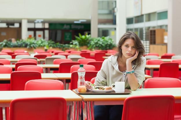 Estudiante triste sentado en la cafetería con bandeja de comida