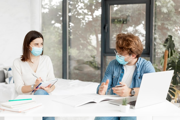 Estudiante y tutor con máscaras médicas en interiores