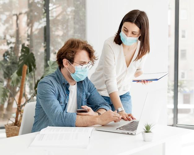 Estudiante y tutor con máscaras médicas