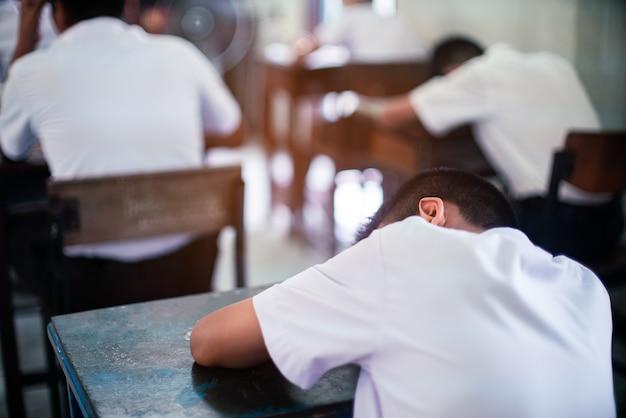 Estudiante uniforme cansado durmiendo en un aula de prueba de examen