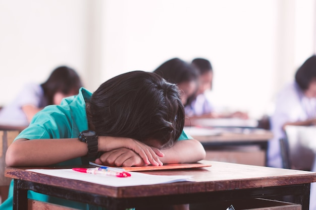 Estudiante de uniforme cansado durmiendo en una prueba de examen en el aula