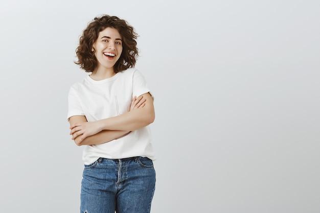 Estudiante universitaria feliz confidente sonriendo con las manos cruzadas
