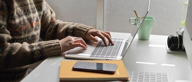 Estudiante universitaria haciendo tesis con pantalla en blanco portátil, teléfono inteligente y papelería en mesa de trabajo blanca