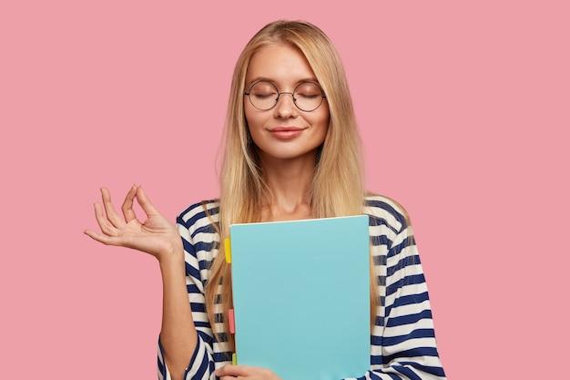 Estudiante universitaria rubia complacida posando contra la pared rosa