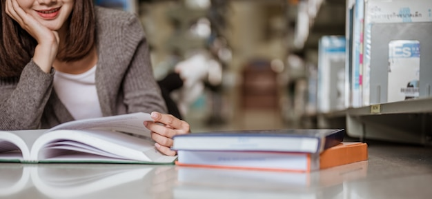 Una estudiante universitaria sentada en la biblioteca de la universidad leyendo un examen con una cara sonriente. concepto de educación, escuela, biblioteca y conocimiento.