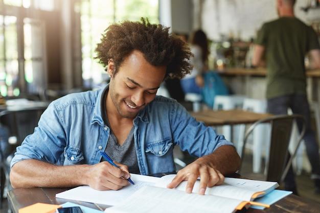 Estudiante universitario afroamericano alegre atractivo que trabaja en la asignación de casa en la cafetería, escribiendo composición o haciendo investigación, con mirada feliz y entusiasta. personas, conocimiento y educación