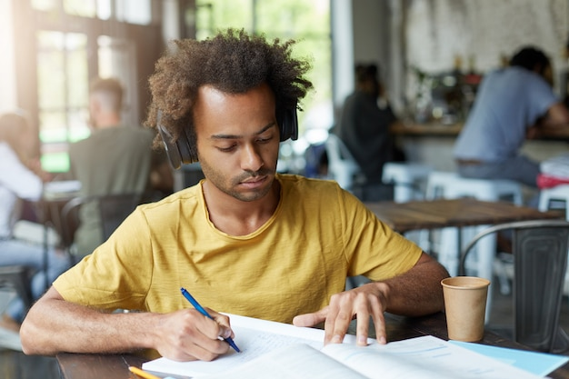 Estudiante universitario afroamericano de moda haciendo deberes en francés en la cafetería, estudiando pronunciación y ortografía, escuchando tareas de audio con auriculares mientras aprende nuevas palabras