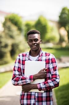 Estudiante universitario afroamericano con portátil en el día soleado en la calle de la ciudad