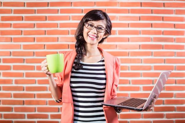 Estudiante universitario asiático con laptop y café