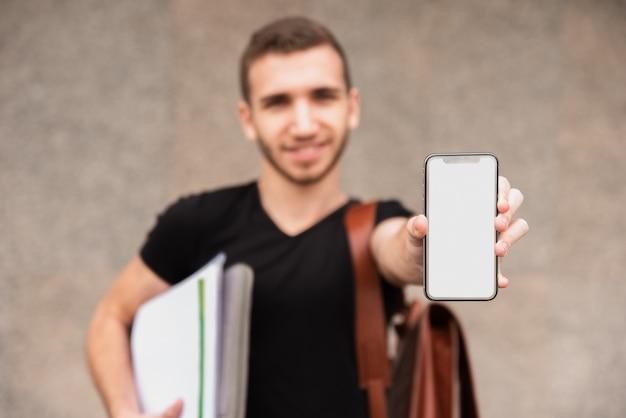 Estudiante universitario borroso mostrando su teléfono