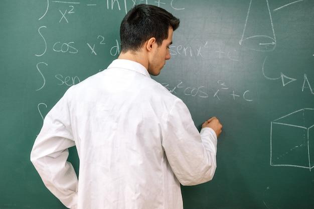Estudiante universitario en clase de laboratorio, con bata blanca, escribiendo en la pizarra.