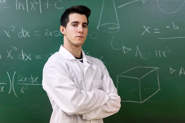 Estudiante universitario en clase de laboratorio. estudiante universitario con bata blanca, de pie delante de la pizarra.
