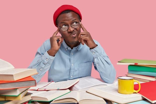 Estudiante universitario contemplativo de piel oscura mantiene ambos dedos en las sienes, frunce los labios y mira con vacilación a un lado, intenta analizar la información en su mente, siendo adicto al trabajo
