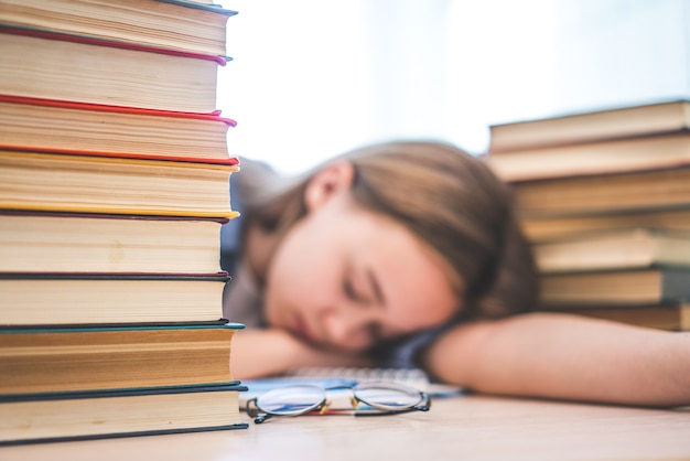 Estudiante universitario estresado, cansado de aprender mucho con libros en preparación de exámenes, abrumado adolescente de secundaria agotada por estudios difíciles o demasiada tarea, concepto de hacinamiento
