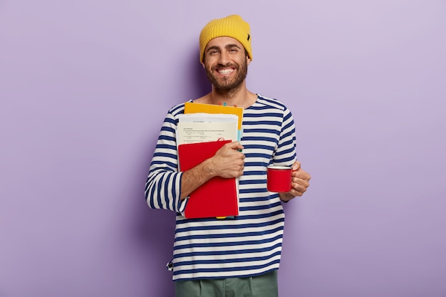 Estudiante universitario feliz lleva papeles y bloc de notas, se prepara para los exámenes, bebe bebidas calientes de la taza