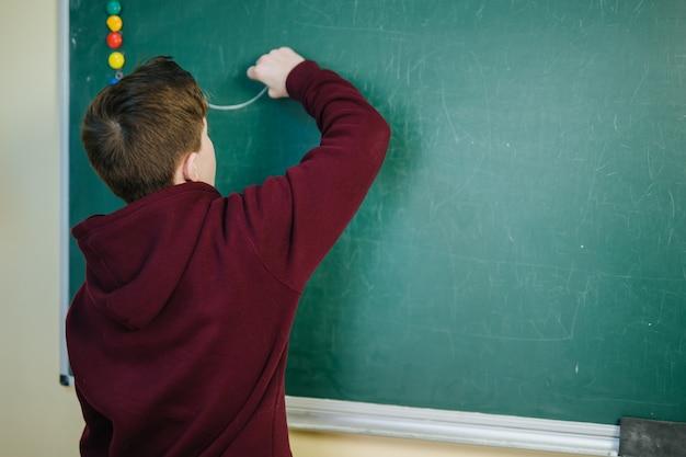Estudiante universitario guapo resolviendo un problema de matemáticas durante el clas de matemáticas