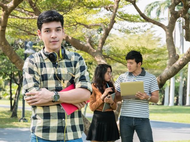 Estudiante universitario joven hermoso que celebra los libros y que sonríe