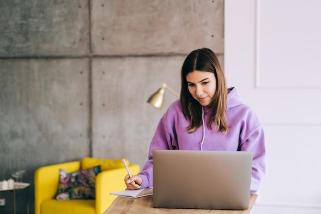 Estudiante universitario joven que estudia con la computadora portátil, preparándose a distancia para el examen de prueba, escribiendo un ensayo haciendo la tarea en casa, concepto de educación a distancia.