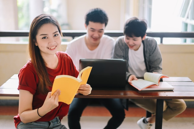 Estudiante universitario lee un libro de un amigo con una computadora portátil sentado en un edificio de la escuela