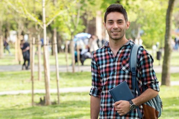 Estudiante universitario con libro al aire libre