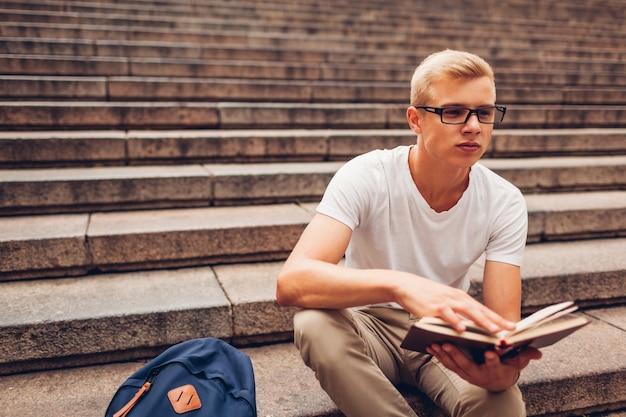 Estudiante universitario con el libro de lectura de la mochila que se sienta en las escaleras y que sostiene los vidrios. chico estudiando al aire libre