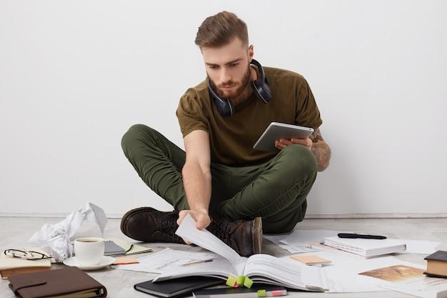 Estudiante universitario masculino beared preocupado con peinado moderno mira atentamente en el libro, sostiene la tableta moderna