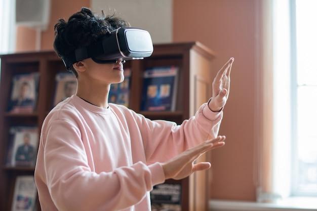 Estudiante universitario móvil en ropa casual y gafas vr tocando la pantalla virtual mientras se mueve en una realidad tridimensional